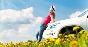 Junge Frau lehnt an Auto - Symbol für Autofrühling