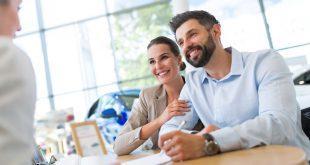 Junges Paar untertschreibbt Vertrag im Autohaus