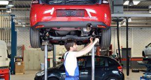 KFZ-mechaniker arbeitet unter Hebebühne -Arbeitsschutz in der Kfz-Werkstatt